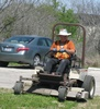 Kirk operating a zero turn mower in the visitor center complex.