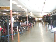 There is a room full of different buggies and carriages.